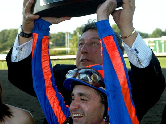 Lion Heartjockey Joe Bravo holds the Haskell Trophy over his head with help of trainer Patrick L. Biancone at Monmouth Park in Oceanport in 2004.