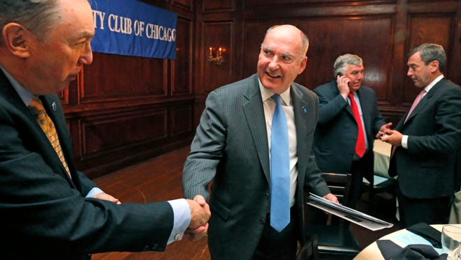 Big Ten Commissioner Jim Delany, right, shakes hands with Paul Green after speaking to the City Club of Chicago on Thursday, Feb. 27, 2014, in Chicago.