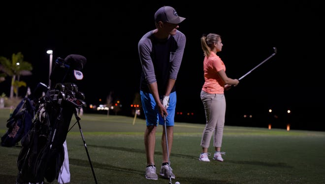 Evan Hipp, 20 years, and Candice Weese, 18 years and a student at FGCU, practice their chipping skills on the practice green at Alico Family Golf in Fort Myers, Sunday evening, December 6, 2015.