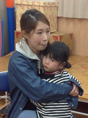 Yumi Kanno, 29, and her daughter Shian, 2, wait at