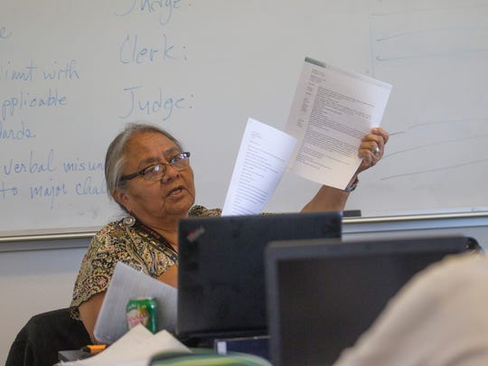 Federal court interpreter and Navajo Technical University adjunct professor Esther Yazzie goes over her students' work Wednesday at the school in Crownpoint.