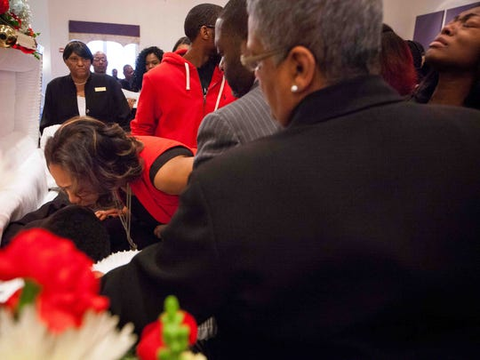 Shareece White, mother of William Rollins VI, 18, who was fatally shot Jan. 24, kisses her son on the forehead as family and friends packed into Ezion Fair Baptist Church for the funeral service.