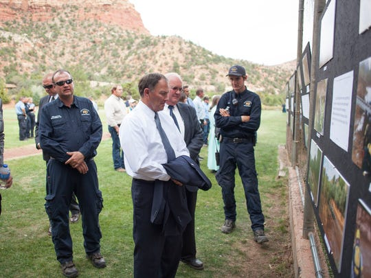 Utah Gov. Gary Herbert, white shirt, reads a memorial wall paying tribute to flash flood victims Saturday, Sept. 26, 2015, as he visits with Hildale Mayor Philip Barlow and other municipal officers.