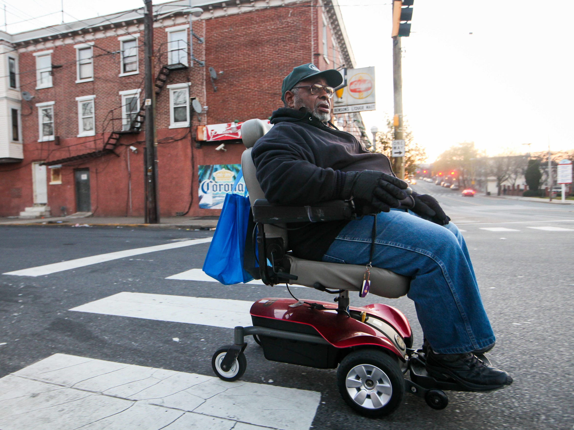 Clarence Raynor, 82, waits for the light at W. 4th and N. Monroe Streets as he rides his motorized wheelchair from his home at Sacred Heart Village to The Fresh Grocer, in Adams Four.
