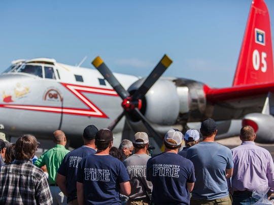 Firefighters stand next to a Lockhead P2V plane at the Cedar City airport during the memorial dedication of Tanker 11 and pilots Todd Tompkins and Ron Chambless, Friday, June 3, 2016.