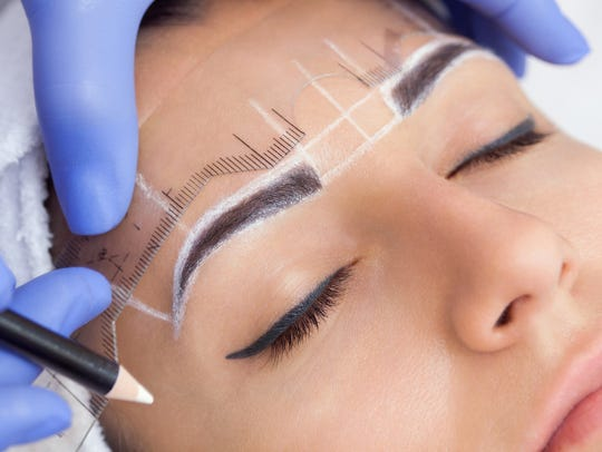 A technician draws and measures prior to microblading