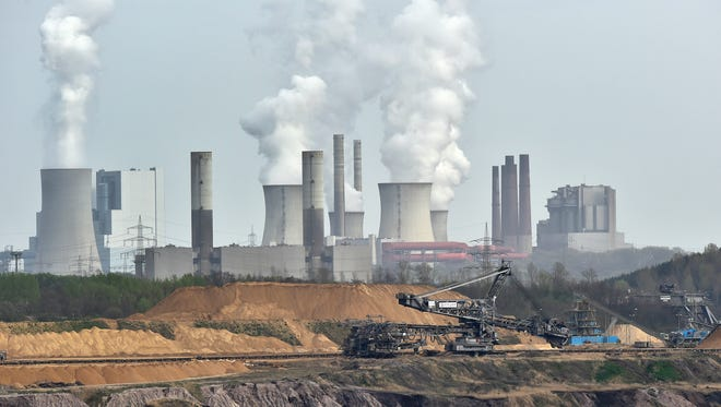 Giant machines dig for brown coal in front of a smoking power plant near Grevenbroich in western Germany in April 2014  The U.N. weather agency says carbon dioxide levels in the atmosphere reached a record high in 2013.