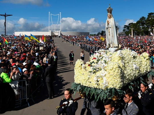 A figure representing Our Lady of Fatima is carried