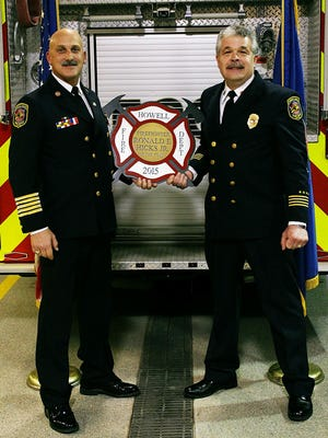 Howell Area Fire Chief Andy Pless, left, presents Deputy Chief Ronald Hicks with the department's Firefighter of the Year award at an annual ceremony Wednesday.