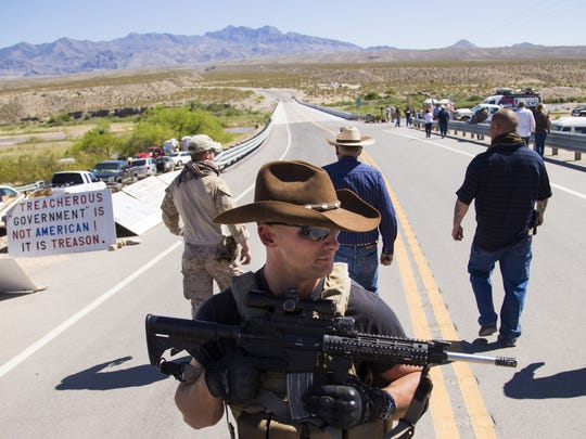 Rancher Cliven Bundy (center rear) leaves a news conference under security by militia near Bunkerville, Nevada, on April 14, 2014.