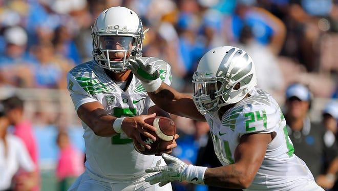 Oregon quarterback Marcus Mariota (right) hands off to running back Thomas Tyner during the second half against UCLA on Saturday, Oct. 11, 2014, in Pasadena, Calif.