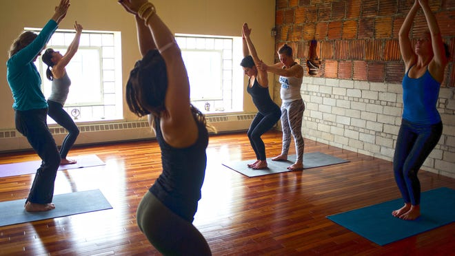 """Kathy McNames adjust the position of Alexa Gould-Kavet during a hour and a half long session held at Yoga Vermont studios in Burlington on Wednesday. """"It's so holistic and it address the mind-body connection,"""" said Gould-Kavet who has been a practioner of many styles of yoga since she was 11 years old."""