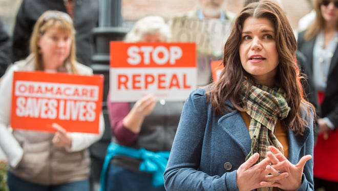 Jessica Hendricks Fisher, right, speaks about being denied health insurance because of her Hodgkin's disease diagnoses during a rally asking Sen. Lamar Alexander to stop his rush to repeal the Affordable Care Act held outside his office in downtown Knoxville on Thursday, Jan. 19, 2017.