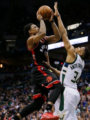 Raptors guard DeMar DeRozan goes up for a shot while being defended by Bucks forward Giannis Antetokounmpo during the first half of Game 6 against the Raptors on Thursday night at the BMO Harris Bradley Center.