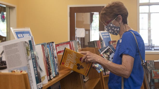 Reed Memorial Library reopened to the public on Monday. Diane Damicone, of Rootstown, wears a mask as she looks through books.