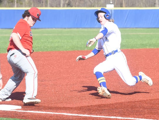 Mountain Home's Gage McClain slides into third base