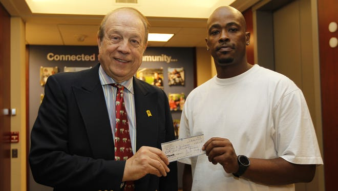 Attorney Michael Hupy (left) presents a reward check for $25,000 to Antoine Buchanan.