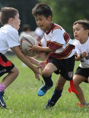 Owen Chow, 8, of Morristown runs the ball against Ridgewood during the Morris Rugby Flag Festival.