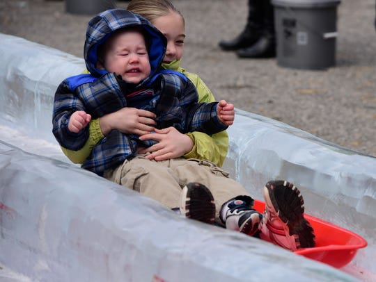 A bundled-up boy and girl slide down the double-wide ice slide at the 2018 IceFest.