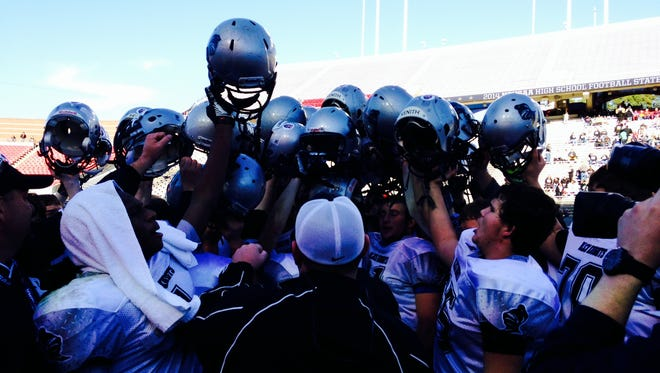 Robbinsville football players break their postgame huddle Saturday as the new NCHSAA 1-A champions in Raleigh.