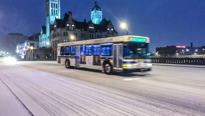 Public bus drives on an icy Broadway.