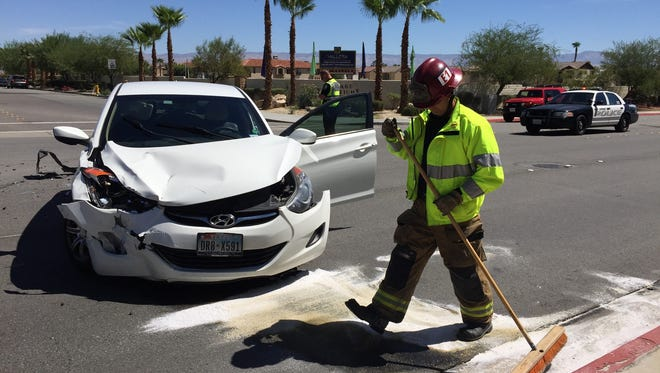 A firefighter helps clear the area of a traffic collision in Palm Springs. Two cars collided on Ramon Road at Calle Palo Fierro.