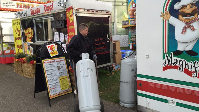 Loren Hart, with Selby's Gas, Lancaster, delivering a propane tank to one of the food vendors at the Fairfield County Fair on Wednesday.