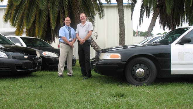 James Johnson (left) and Ernie Hutman stand with the retired police cars donated to Brevard Public Schools.