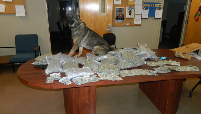 ISP K9 Drogos sits with evidence seized in a Friday drug bust on I-69.