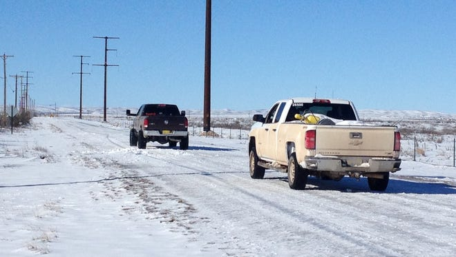 Drivers try to navigate a farm road covered in snow and ice after the weekend snowstorm.