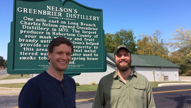 Andy Nelson, left, and Charlie Nelson stand in front of the historical marker for their family's original distillery named after the town of Greenbrier, Tenn.