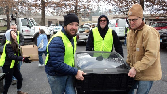 Asheville GreenWorks staff and volunteers load old TVs at a past Hard 2 Recycle event. The free event will be Jan. 16 in two West Asheville locations.
