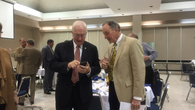 Rapides Parish Sheriff William Earl Hilton (left) looks at his cellphone with Charles Chartier on Tuesday after the Rotary Club of Alexandria meeting.