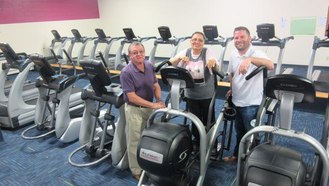 Cancer survivor Carmen Soto demonstrates an elliptical trainer for Gary Galloway, president, YMCA Board,  (left) and Tim Chew, first vice president of the YMCA Board and annual campaign chair, (right) in the YMCA of Vineland's family fitness center.