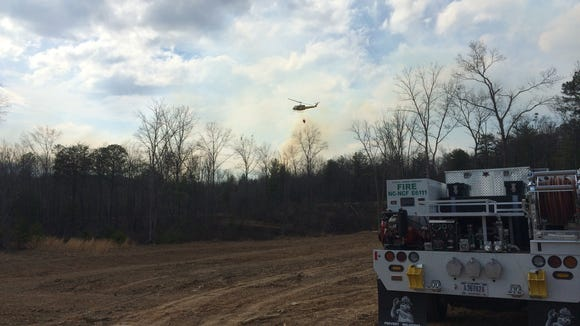 A helicopter assists with firefighting efforts March 24 on the North Peak Fire burning in McDowell County north of Lake James.