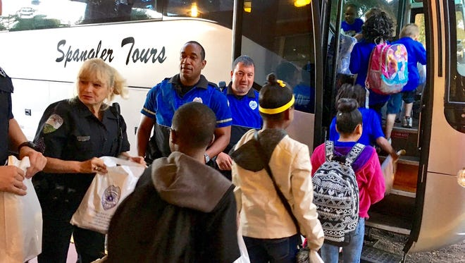 Alexandria Police Department officers hand D.F. Huddle Elementary students activity bags as they board a charter bus Thursday to go to New Orleans as a reward for earning the most Accelerated Reader points.