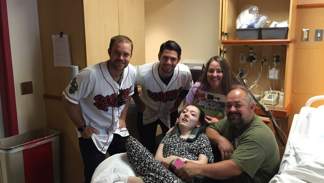Nashville Sounds Daniel Coulombe (left) and Tucker Healy pose with 15-year-old Savannah Dill and her mother April Dill and father Howard Dill.
