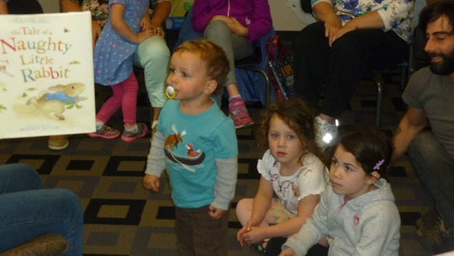 """Henry Burrus pays attention to """"Peter Rabbit: The Tale of a Naughty Little Rabbit"""" by Beatrix Potter as Lily (seated, left) and Neko Faust look on at Franklin Township Library."""