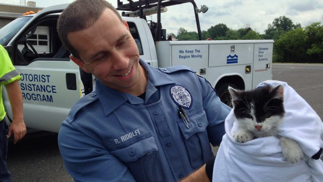 Delaware River Port Authority policeman Richard Ridolfi holds a kitten he rescued after a driver threw it from a car window onto the Walt Whitman Bridge. The kitty now has a new home.
