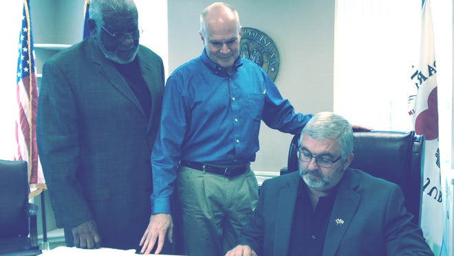 Rapides Parish Police Jury President Craig Smith (seated at right) looks over Police Jury budget figures as Juror Theodore Fountaine (left) and Treasurer Bruce Kelly (center) look on. The Police Jury's budget has taken a hit from reduced funding because of changes in the District Attorney's Office operations.