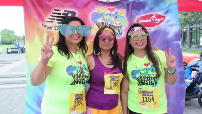 Nolita Schoonover, Shirley Stickles and Lea Estrabo take part in the photo booth at the High Street Hustle on Aug. 15, 2015.