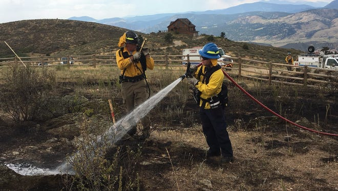 Firefighters douse the remnants of the Stag Hollow Fire, which burned 4.7 acres on Milner Mountain, in this file photo. The Larimer County Commission extended a fire ban in the unincorporated county through Sept. 15.