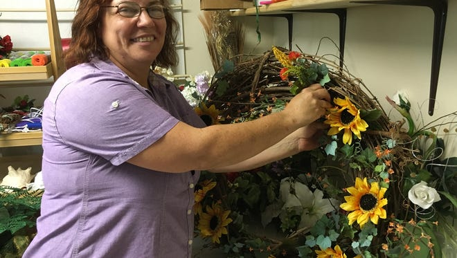Wendy Liford, owner, Every Loving Bloom, puts the finishing touches on a fall wreath at her new shop.