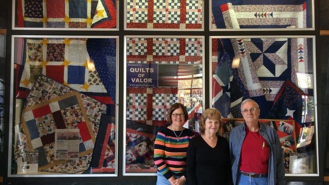Sue Swan, Lou Russell and Tommy Forrest stand at the Quilts of Valor display in the lobby of the Anderson County Library.
