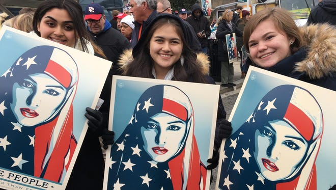 Three students from Indio High School hold signs promoting inclusiveness during the inauguration of Donald Trump.