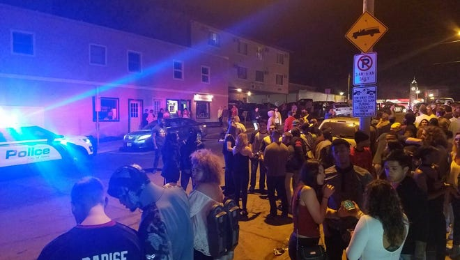 Crowds gather outside AJ's Ultra Lounge, on Chamberlain Street, in Ames as police investigate an overnight shooting that left three injured.