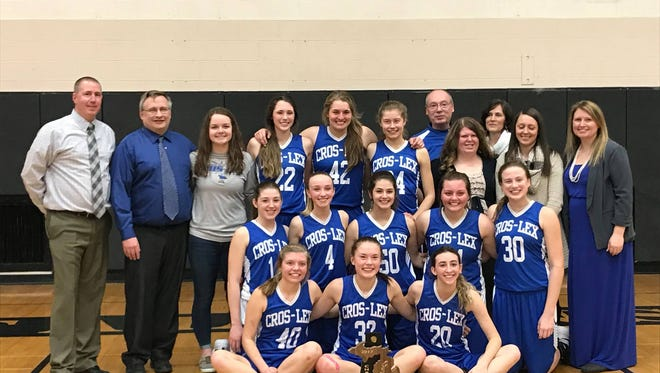The Croswell-Lexington girls basketball team takes a photo after claiming its latest district title.