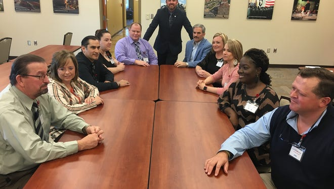Some of the key staffers involved in 101 Jobs for the 101st. shown in a meeting, from left, are Dale Peters, Kim Rye, Francisco Vasquez, Brandi LaPoint, Lance Maass, John Clement (standing), Charlie Koon, Eve Osborn, Heather Brooks, Teshia Dennis and John Carey.