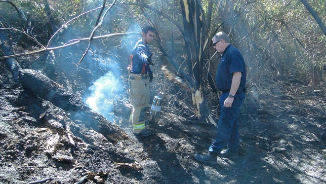 The Tempe Fire Department monitors hot spots the day after the fire in Papago Park that occurred June 15, 2016.
