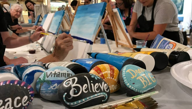 Art therapy painting class participants create soulful beach scenes. They also painted inspiring rocks to share by placing them around Tallahassee in support of the Tallahassee Rocks movement.